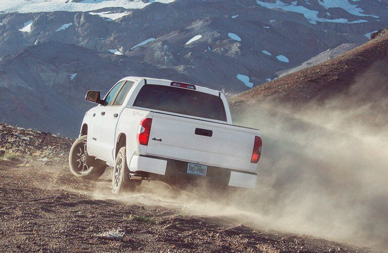 white 2017 Toyota Tundra driving up rocky hill in mountains rear view