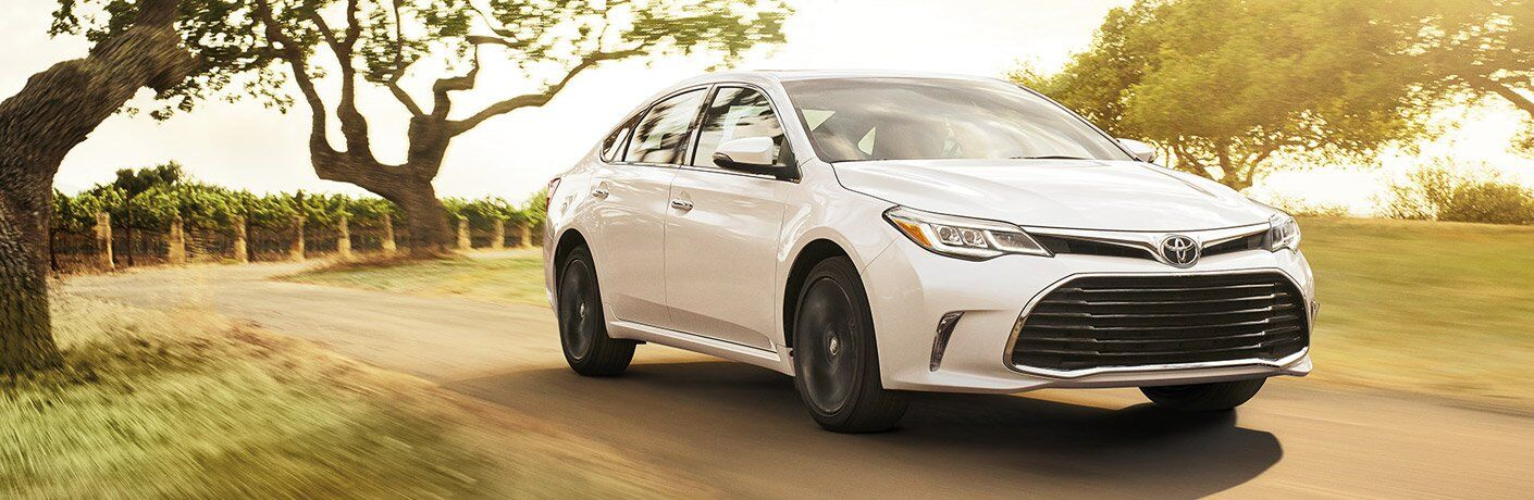 White 2017 Toyota Avalon driving down country road