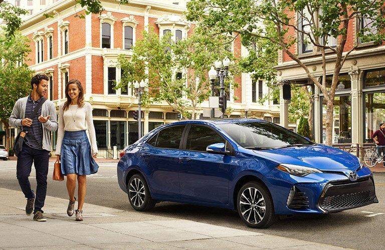 young couple walking away from parked blue 2017 Toyota Corolla
