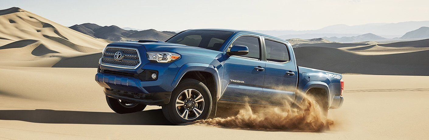 blue 2017 Toyota Tacoma driving through desert sand