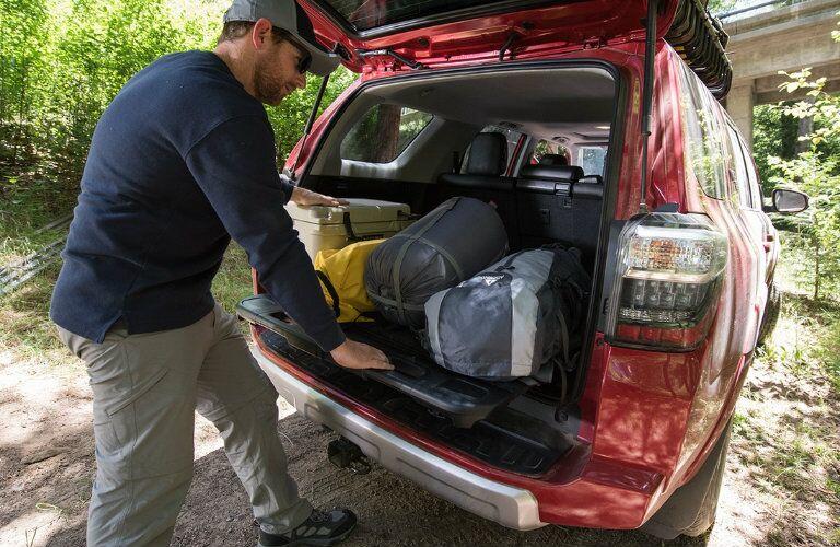 man unloading cargo from red 2017 Toyota 4Runner