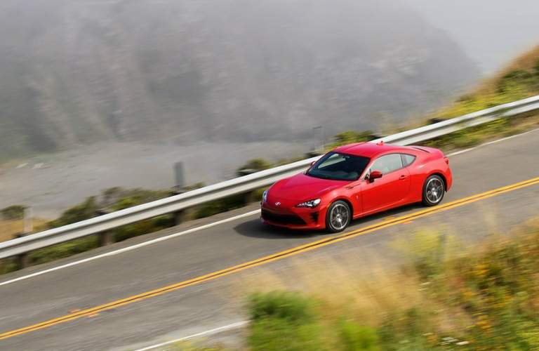 red 2017 Toyota 86 driving near cliff