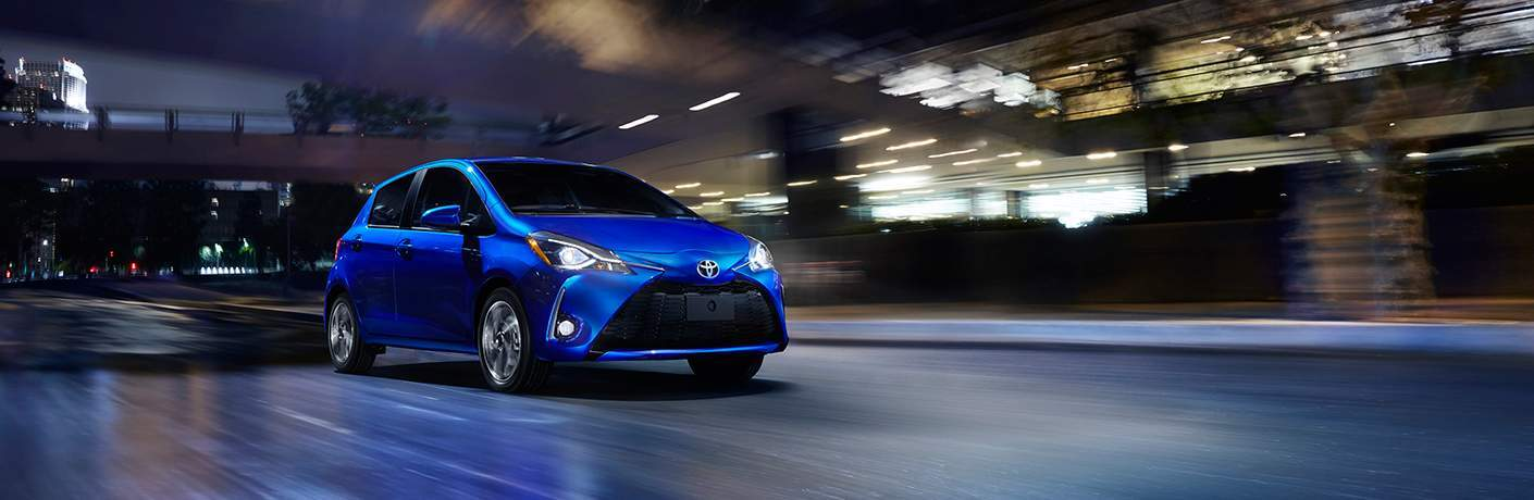 blue 2018 Toyota Yaris driving down street at night exterior front view