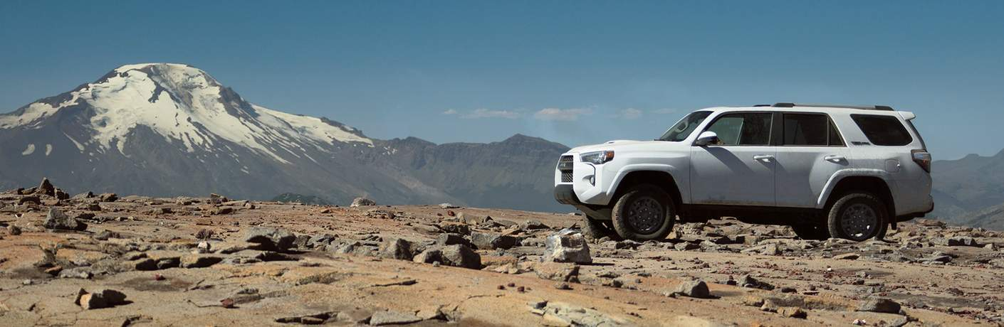 white 2018 Toyota 4Runner on rocky surface with mountain background