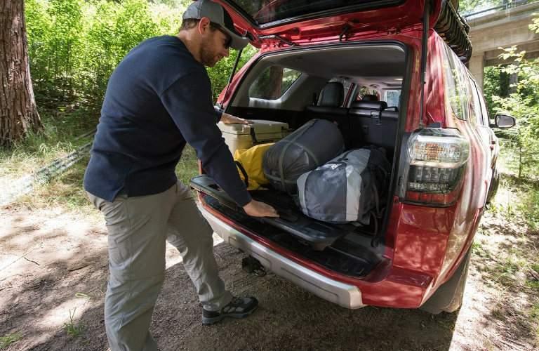 man unloading cargo from back of 2018 Toyota 4Runner
