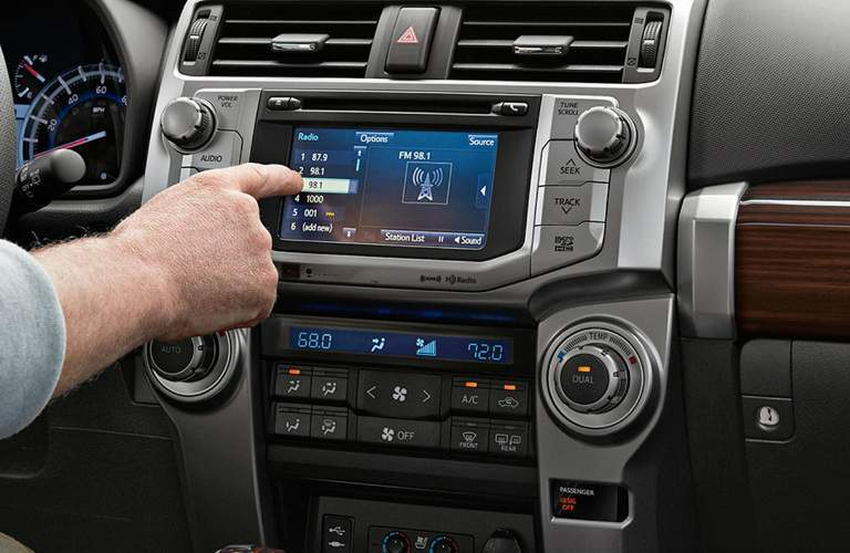 hand using center console screen in 2018 Toyota 4Runner