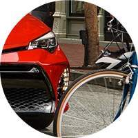 front grille of red 2018 Toyota Corolla and front wheel of bicycle