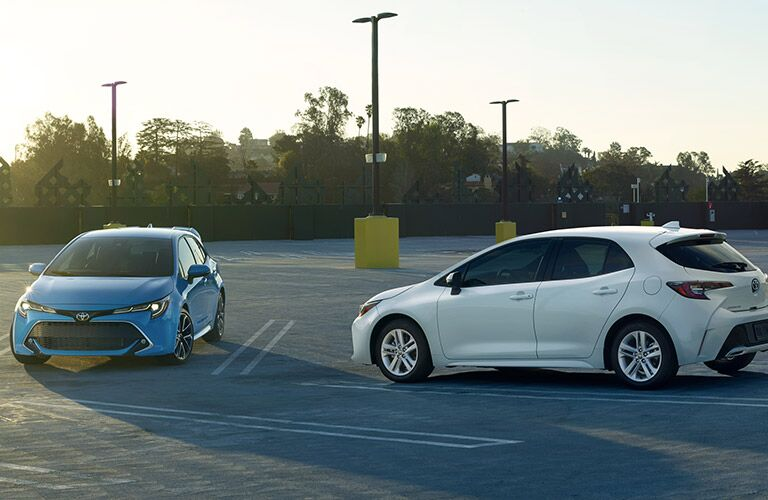 2 2019 Toyota Corolla Hatchbacks exterior front fascia and drivers side exterior back fascia and drivers side angled towards each other in empty parking lot