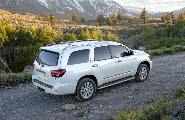 2019 Toyota Sequoia exterior back fascia and passenger side on dirt road with mountains in background