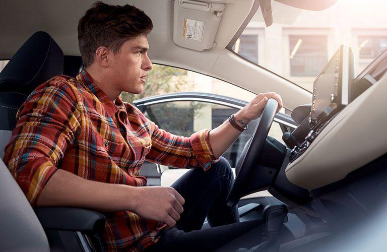 man sitting in driver seat of 2020 corolla hybrid