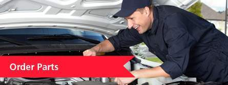 mechanic smiling while working under hood of car
