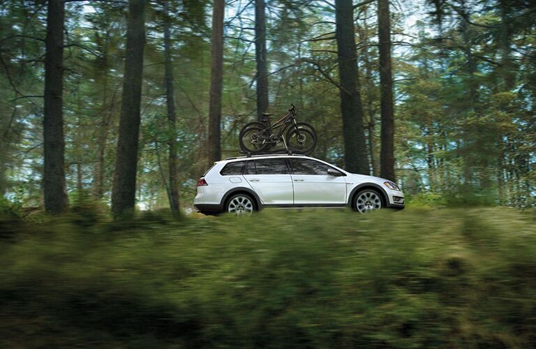 2018 Volkswagen Golf Alltrack driving with bike on roof rails through forest