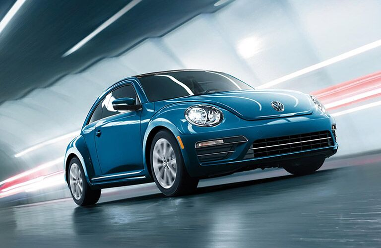 2018 Volkswagen Beetle exterior shot blue driving through a tunnel highway with blurring lights