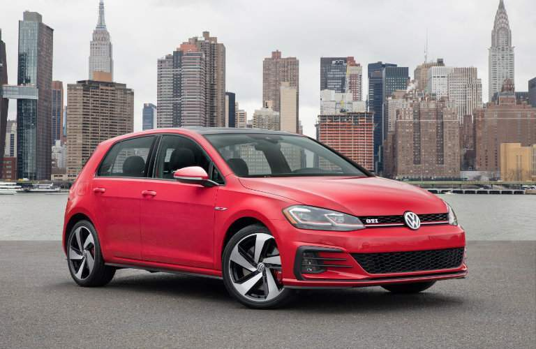 2018 Volkswagen Golf GTI exterior shot red paint color parked on a beach with a cityscape background