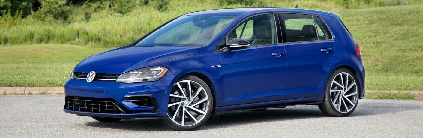 2018 Volkswagen Golf R exterior shot dark blue paint job parked in the middle of a country road surrounded by fields of green grass