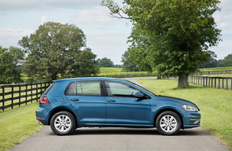 2018 Volkswagen Golf side shot parking on country road with trees and fences