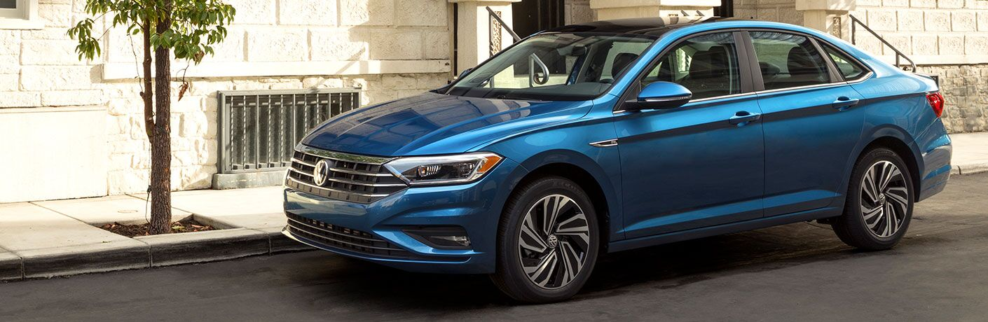 2019 Volkswagen Jetta exterior shot blue paint job parked on a city street next to a white brick building and a planted tree