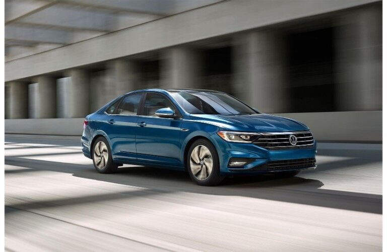 2019 Volkswagen Jetta exterior shot driving through a city with a blurry concrete background