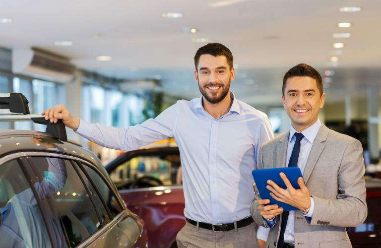 sales man and customer at car dealership