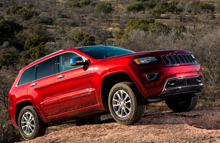 Red 2014 Jeep Grand Cherokee climbing a hill