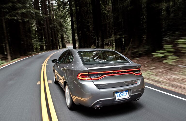 Rear view of Dodge Dart driving on tree-lined road