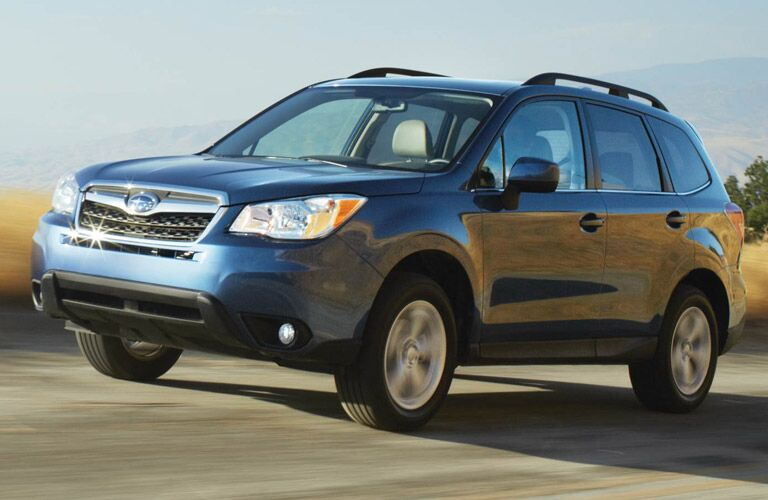 Blue Subaru Forester driving on grassy road