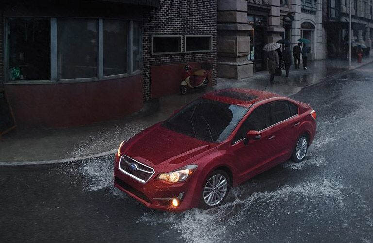 Red Subaru Impreza driving through flooded street