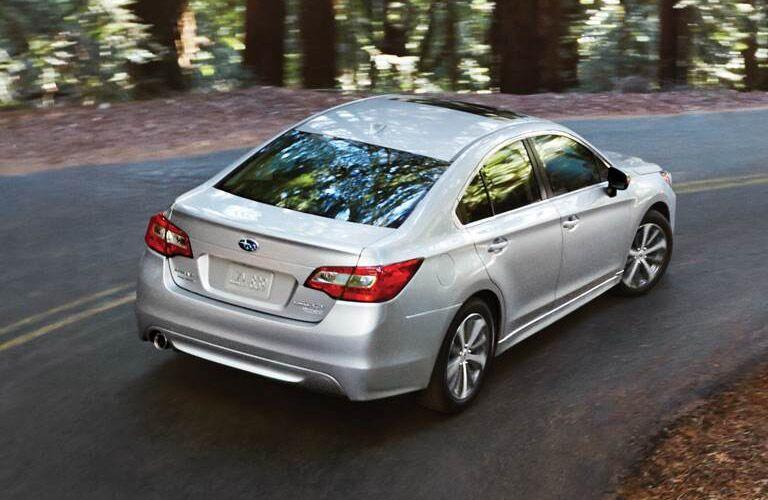 Subaru Legacy sedan driving on wooded country road