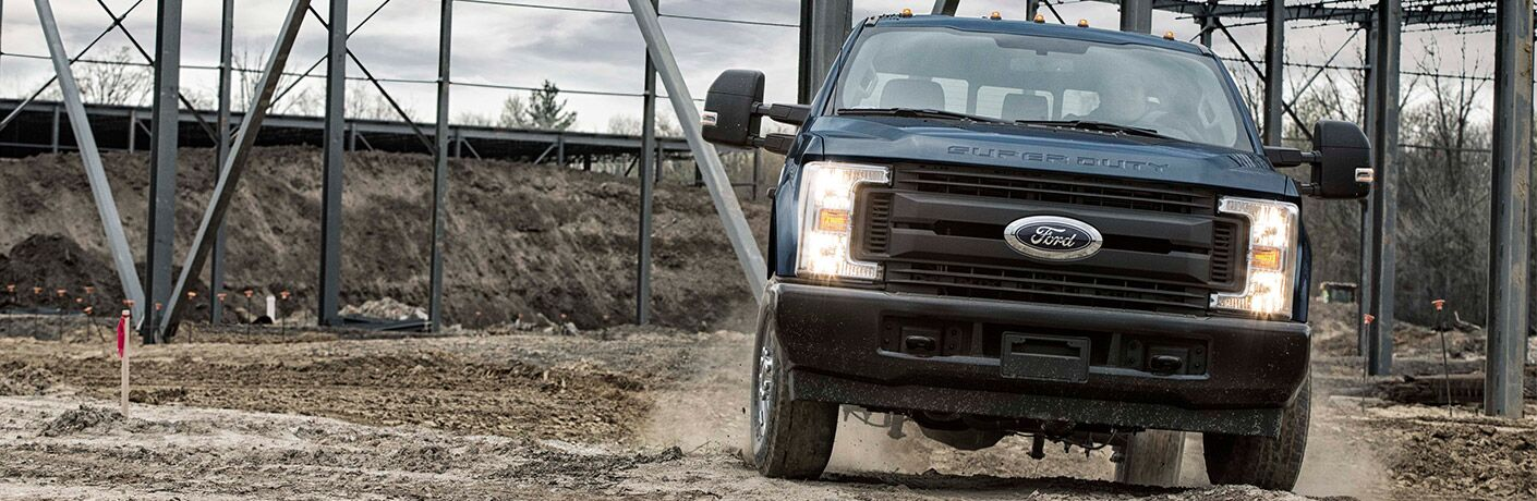 Blue Ford Super Duty driving on worksite