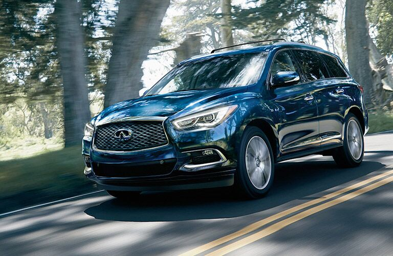 Blue INFINITI QX60 driving on tree-lined road