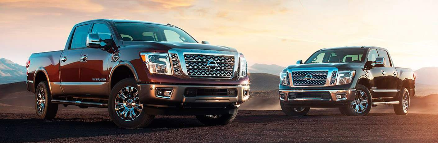 Two Nissan Titan models parked on desert terrain with mountain peaks in background