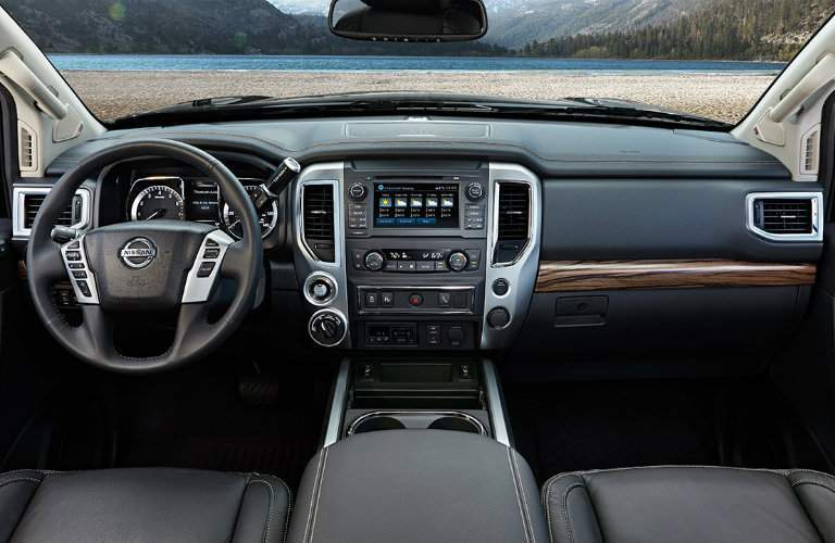 Steering wheel and center touchscreen of Nissan Titan pickup with front row of seating visible