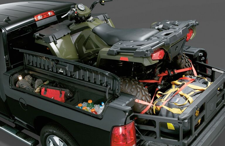 ATV parked in back of 2018 RAM 1500 with cargo management systems prominent