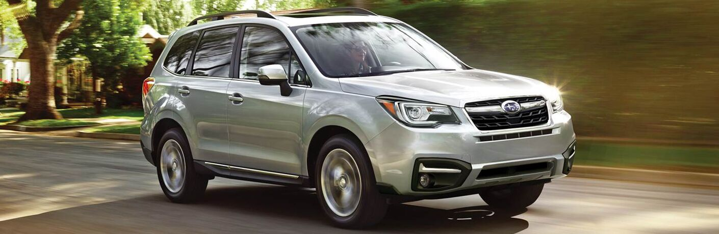 Silver Subaru Forester driving down forested road