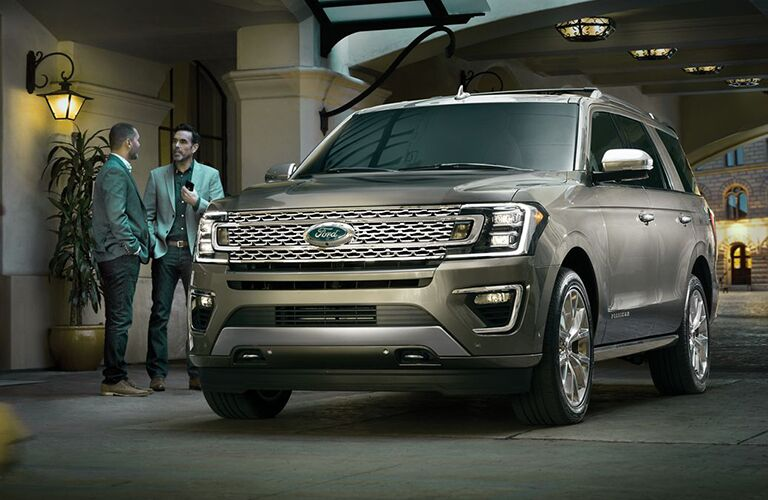 Two men talking next to 2019 Ford Expedition