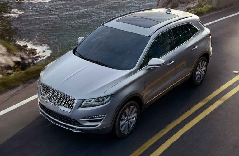 Overhead view of silver 2019 Lincoln MKC driving on two-lane road