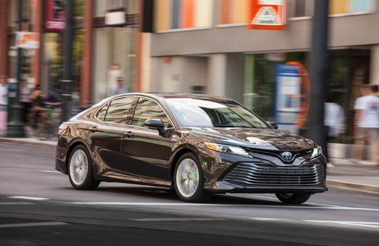 2020 Toyota Camry Hybrid driving down city street from exterior passenger side
