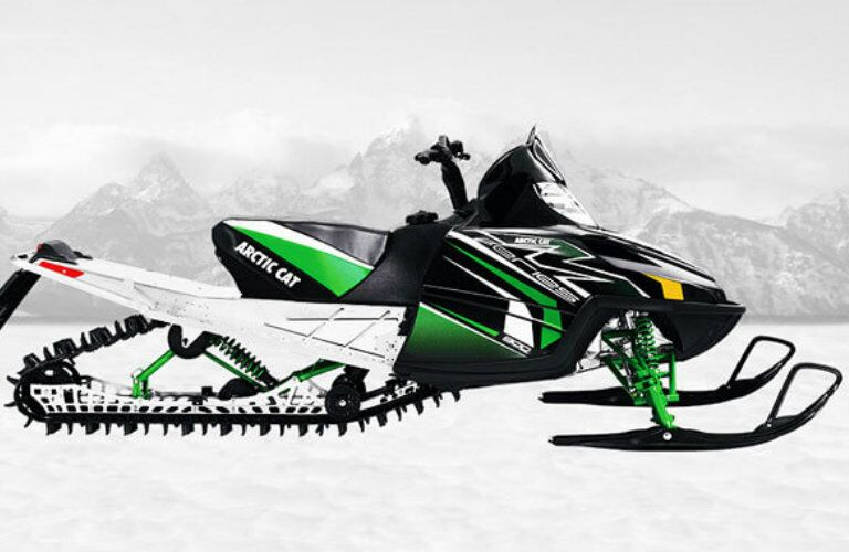 Profile view of black and green Arctic Cat M8 snowmobile