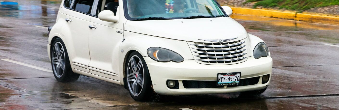 White Chrysler PT Cruiser driving on rainy city road