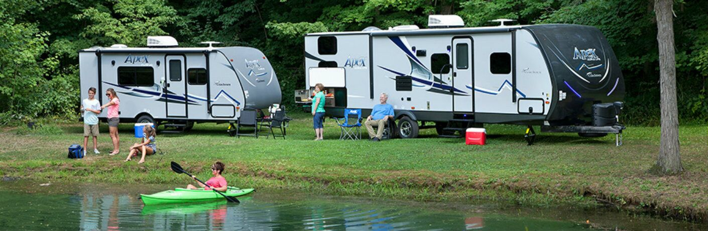 Family relaxing at the lake with Forest River Apex camper in background