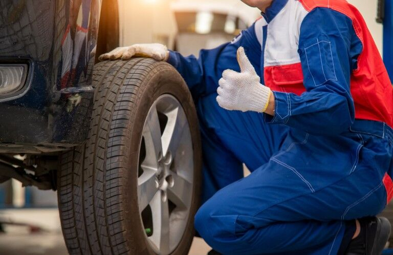 Mechanic giving thumbs up by tire