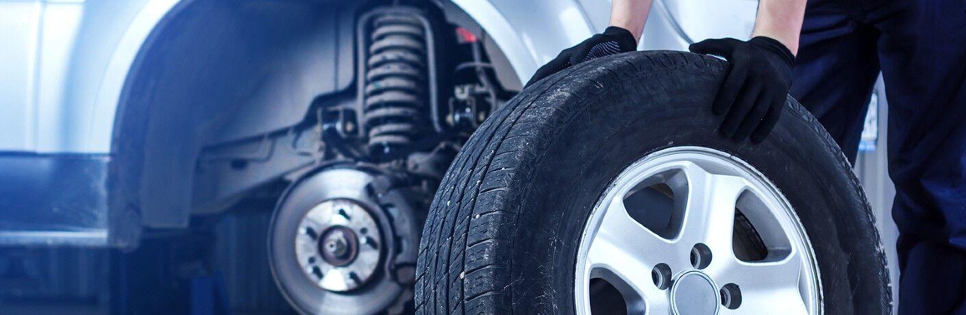 Mechanic holding tire near vehicle