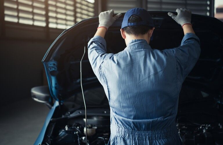 Mechanic looking under hood of car