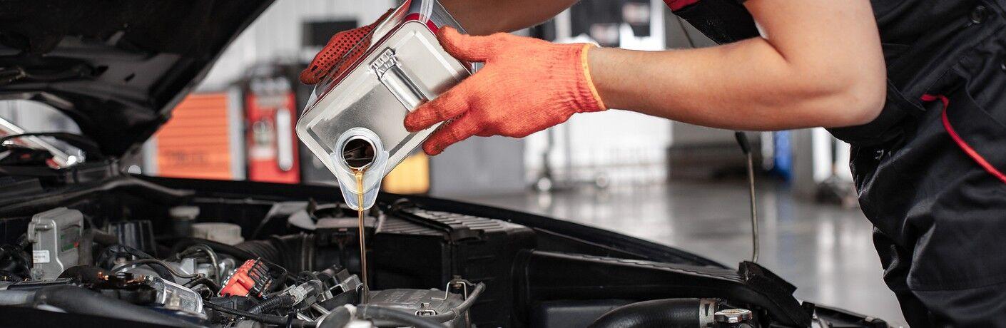 Mechanic adding oil to engine