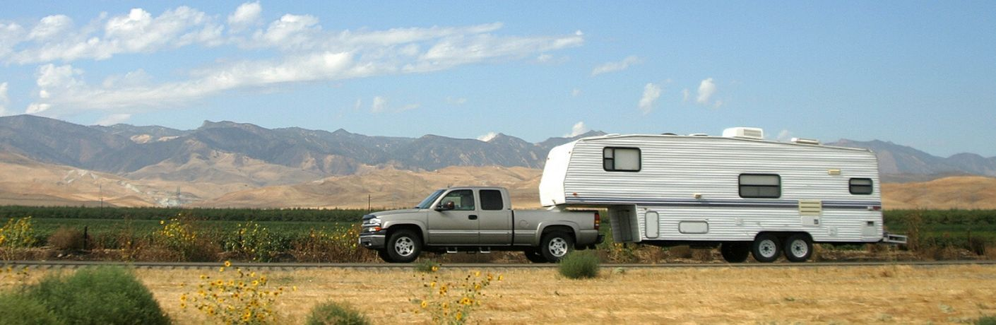 Truck towing fifth wheel in front of mountain range