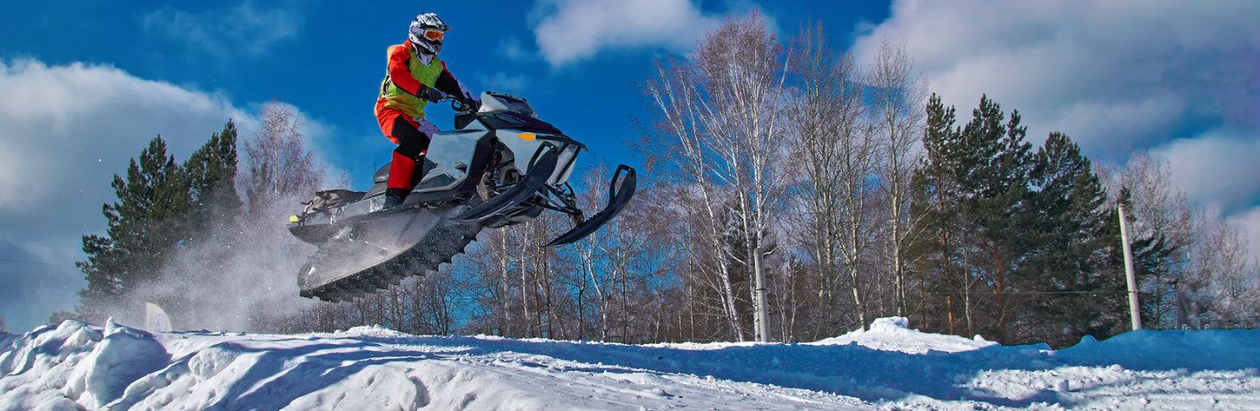 Man jumping snowmobile over hill