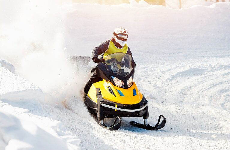 Individual driving yellow snowmobile on snowy terrain