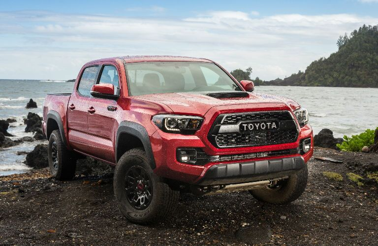 Red 2017 Toyota Tacoma by body of water