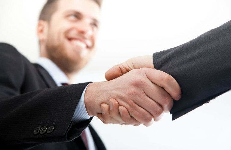 Firm handshake with a smiling man in view