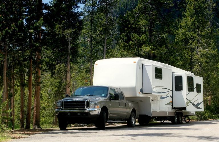 Truck towing fifth wheel camper trailer in campground